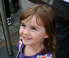Image:  Smiling young girl with purple top